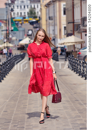 Cute girl walks in the middle of the street 54204800