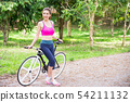 Asian woman with a bike in the park. 54211132
