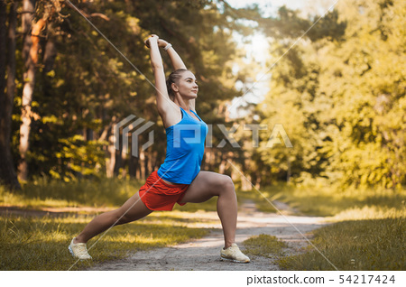 Pretty woman athlete doing exercises before jogging through the woods 54217424