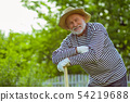 Man smiling while standing near shovel after working in garden 54219688