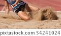 Female athlete long jump landing sand spray 54241024