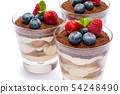 Classic tiramisu dessert with blueberries and raspberries in a glass isolated on a white background 54248490