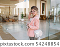 Happy young woman entering glass door into modern 54248854