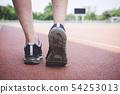 Runner feet of athlete running on road track, 54253013
