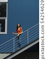 Beautiful young woman with cup of coffee standing on stairs against blue wall 54254629