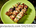 Juicy grilled chicken skewers on green plate on summer day 54256023