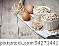 Fresh chicken eggs, oat flakes in ceramic bowls 54271441