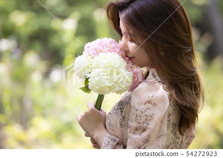 꽃송이를 들고 있는 여성 54272923