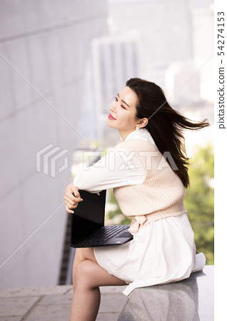 노트북을 무릎에 놓고 있는 여성 54274153