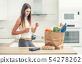 Young woman in home kitchen checks the bill.  54278262