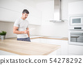 Young man in home kitchen with tablet 54278292