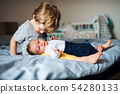 A small boy with a newborn baby brother at home. 54280133