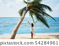 Back view of happy young woman enjoy her tropical beach vacation standing under palm tree 54284961