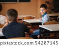 Cute boy lool arround in class room. Back view of boys 54287145