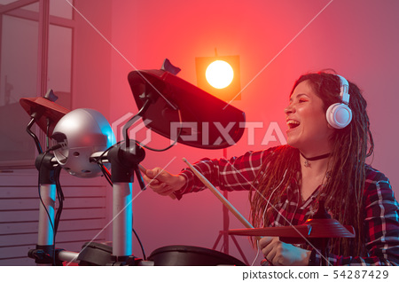 Emotions, music, hobbies and people concept - young woman playing the electronic drum set in studio 54287429