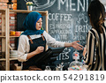 arabic waitress recommending businesswoman 54291819