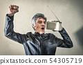 Man rejoicing listening to radio 54305719