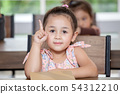 Cute little girl student pointing finger up in 54312210