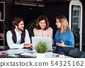 A group of business people sitting in an office, using laptop. 54325162