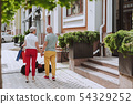 Smiling adult couple with two black scotch terriers in the city 54329252