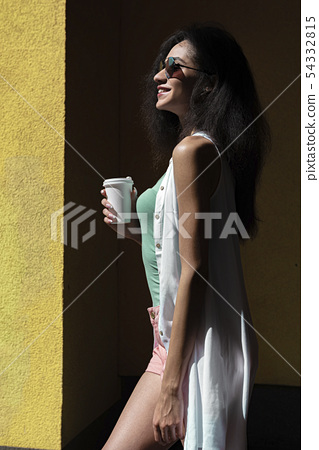 Beautiful brunette girl with cup of coffee standing against yellow wall 54332815