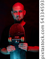 Skateboarder in black shirt with skateboard on neon light background 54334593