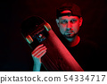 Skateboarder in black shirt with skateboard on neon light background 54334717