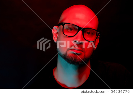 Attractive bald man with beard in glasses on neon light background 54334776