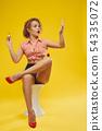 Model sitting, applying red polish, looking at nails. 54335072