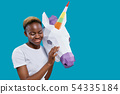 African woman holding 3D paper unicorn head. 54335184