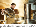 Brewer looking in metallic brew kettle with steam. 54335455