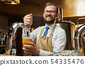 Positive bartender pouring lager beer in glass. 54335476