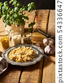 Salad of grated cheese with capers and corn  with basil on wooden table 54336647