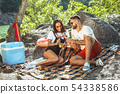 Young couple having picnic at riverside in sunny day 54338586