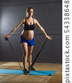 Pregnant woman exercising with resistance band 54338648