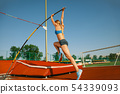 Female high jumper training at the stadium in sunny day 54339093