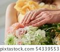 把他們的手放的新娘和新郎在花束上 54339553