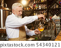 Barman pouring light beer in glass with beer tap. 54340121