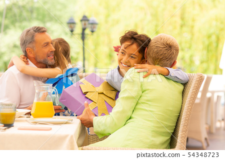 Beaming girl and boy hugging grandparents after getting presents 54348723