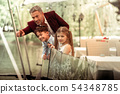Excited cute son and daughter looking at ducks in lake with father 54348785
