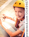 Joyful cute young lady in yellow helmet entertaining herself with smartphone app 54349467