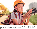 Focused long-haired girl in orange helmet chatting on a smartphone 54349473