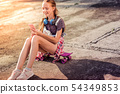 Joyful good-looking little girl in summer outfit wearing sneakers 54349853