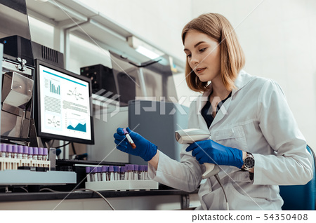 Smart blonde woman holding a test tube with blood 54350408