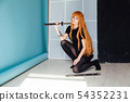 young woman in japanese anime cosplay, holding samurai sword. 54352231