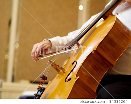 A man playing the cello 54355264