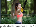 Pretty young girl doing sports on the playground with TRX . Healthy lifestyle, training on trx 54368673