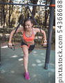 Pretty young girl doing sports on the playground with TRX straps. Healthy lifestyle, training on trx 54368688