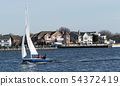 Two person sailboat moving quick i a harbor in 54372419