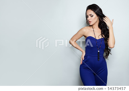 Woman in jumpsuit posing against white wall 54373457